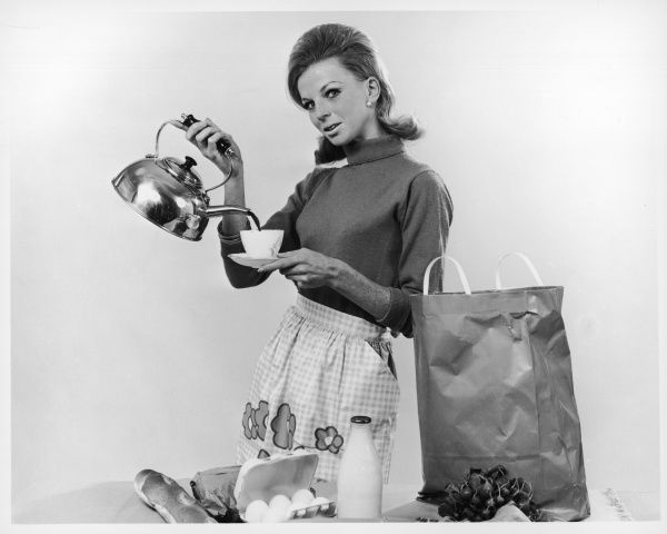 Lady poses while pouring tea. The groceries lie partially unpacked on the table