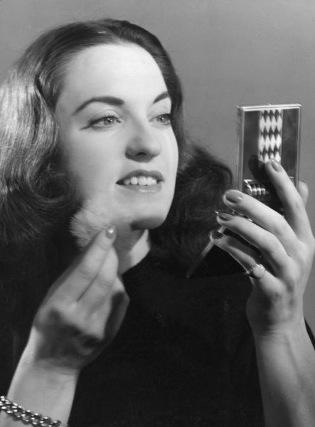 A brunette with a centre parting powders her chin with a powder puff and a stylish powder compact. Date: 1940s