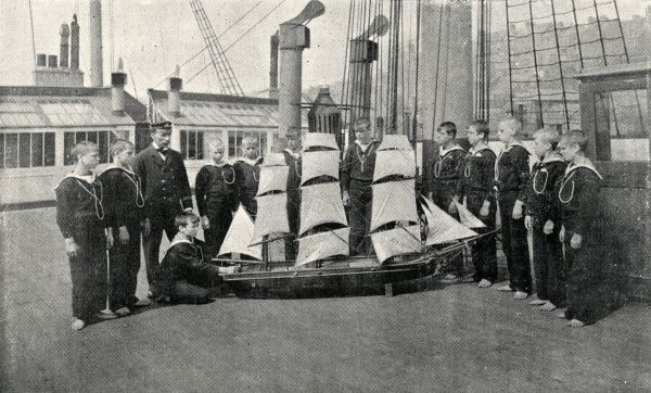 Boys taking part in a practical seamanship class using a large model boat on the Training Ship Wellesley, on the River Tyne at North Shields, Northumberland