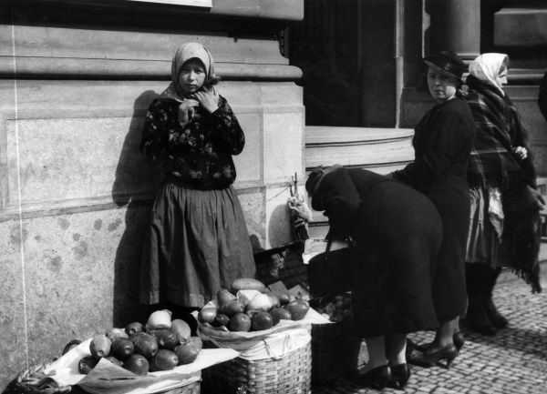A peasant girl selling fruit and vegetables on a stall in Prague, Czechoslovakia. Date: 1930s