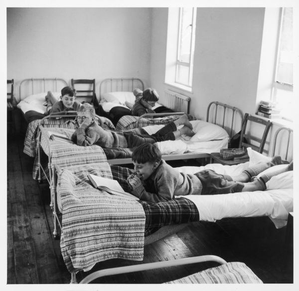 Boys lying on their beds in a dormitory