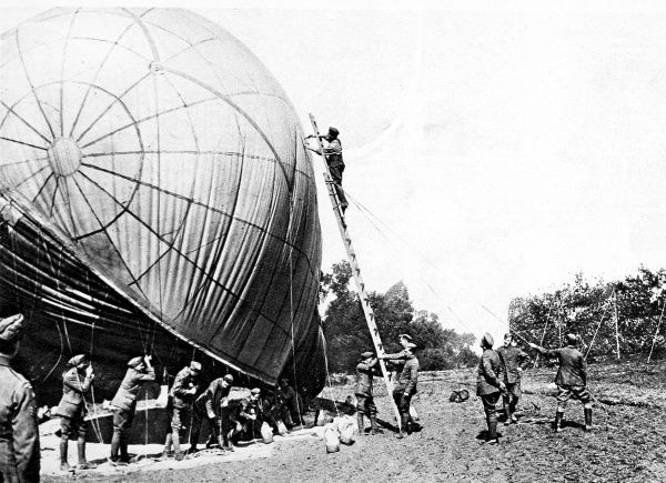 Allied soldiers photographed putting the finishing touches to the envelope of a kite-balloon shortly before take-off. Such balloons remained tethered to the ground and were used to observe the surrounding terrain from a basket suspended beneath