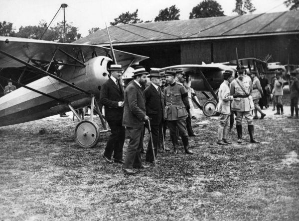 President Raymond Poincare (1860-1934) and others watching a flight at Villacoublay, Seine et Oise, north central France, towards the end of the First World War. Date: 25 June 1918