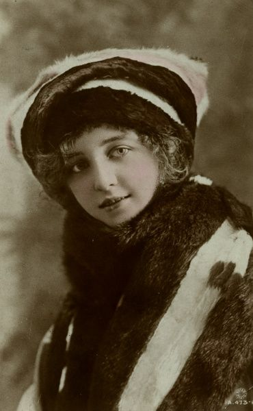A pretty young woman in a fur coat and matching fur hat. Date: early 20th century