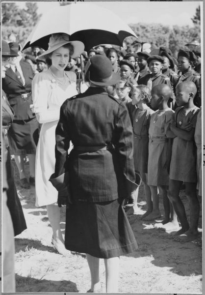 ROYAL TOUR OF SOUTH AFRICA & RHODESIA: Princess Elizabeth (later Queen Elizabeth II), looking elegant under a parasol, inspecting Girl Guides at Maseru, Basutoland