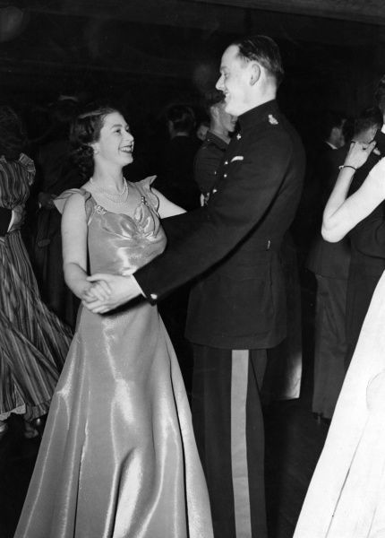 Princess Elizabeth (Queen Elizabeth II) attending a ball held at the Old House Hotel in aid of the NSPCC. She is pictured smiling as she dances with Captain Joshua Rayley of the Grenadier Guards. Date: 1946