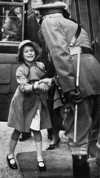 Princess Elizabeth is seen being greeted on her arrival at the daylight rehearsal of the Aldershot Tattoo, at which 50,000 school children were present.  1935
