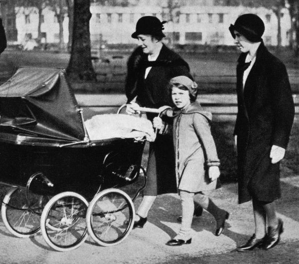 The Princess and her two nurses take her baby sister, Princess Margaret, for a stroll in the spring sunshine. 1933