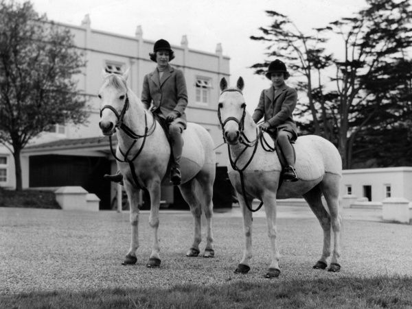 Princess Elizabeth (Queen Elizabeth II) and Margaret on horseback in the ground of Royal Lodge, Windsor c. 1940. Date: c.1940