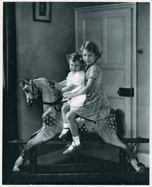 Princess Elizabeth and Princess Margaret photographed on a rocking horse. Date: 1937