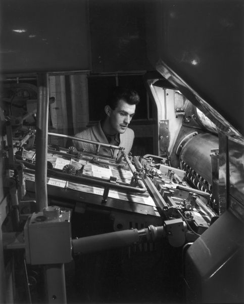 A printing machine operator checks proofs, as they leave the press. A fine study in concentration. Photograph by Heinz Zinram