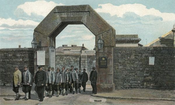 A group of prisoners and their guards pass through the main gate of Dartmoor Prison, Princetown. Date: 1906