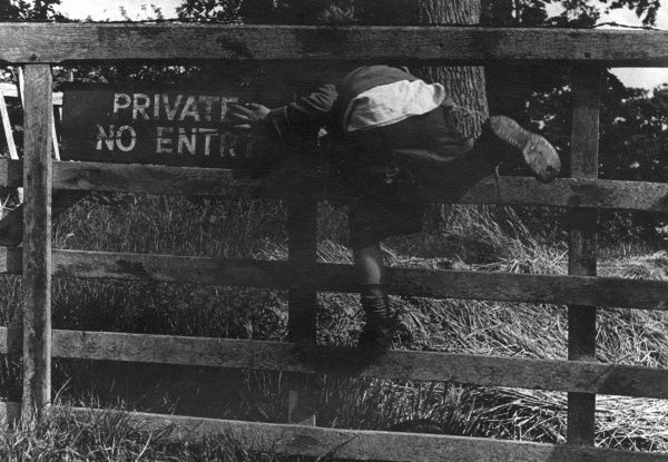 A mischievous boy ignores a sign on a gate stating, 'Private - No Entry' and squeezes through. c.1945