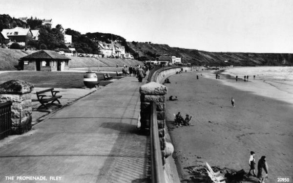 View along the Promenade at Filey, North Yorkshire, with a few people on the beach. Date: 1940s