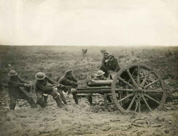 Men pulling and jacking a field gun stuck in the mud during bad weather on the Western Front in Flanders during the First World War. They are trying to get it into a new position for firing. Date: 1914-1918