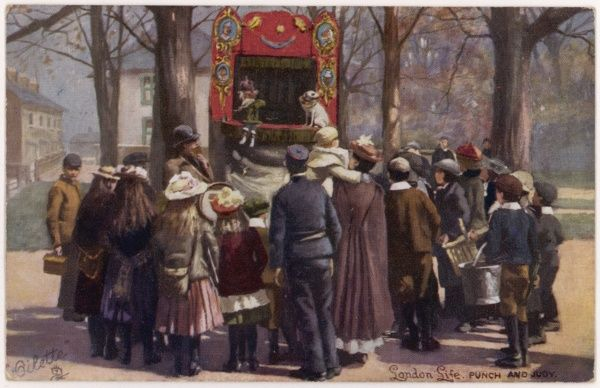 Children crowd round a Punch and Judy show in a London park
