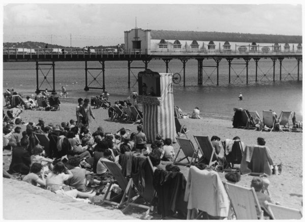 Rows of holidaymakers, mostly seated in deckchairs, watch the Punch and Judy show on the beach at Paignton, Devon, England