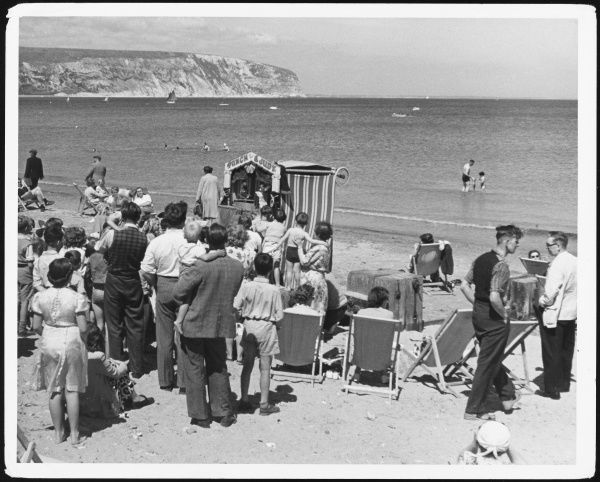 A crowd gathers on the beach to watch a Punch and Judy show