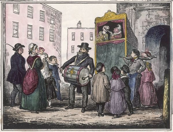 A Punch & Judy show attracts an audience in a street