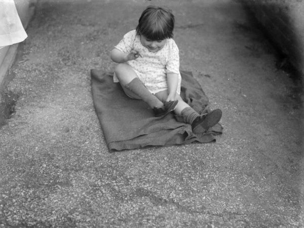 A National Adoption Society little girl, sitting on a blanket, blanket, learns how to put on her own shoes. Date: early 1930s