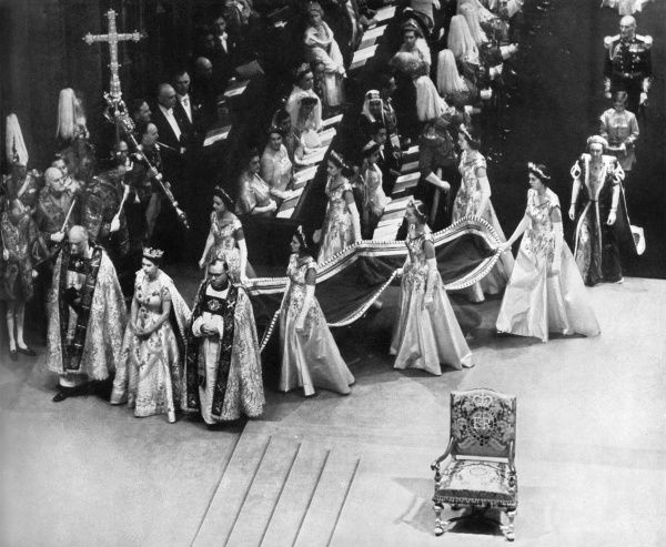 Accompanied by the Bishops of Bath and Wells and Durham, Queen Elizabeth II moves up Westminster Abbey, passing the throne. Date: 1953