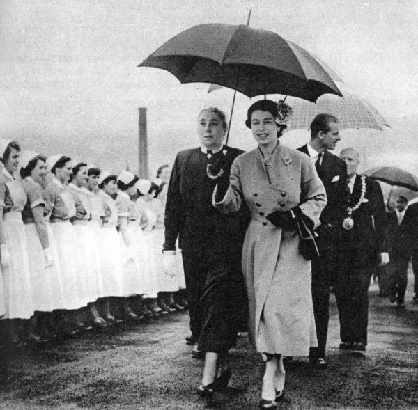 The Queen at the Royal Infirmary, Dundee, Scotland. She is accompanied by the Matron, Miss O. A. Day, and followed by the Duke of Edinburgh. Date: 1955
