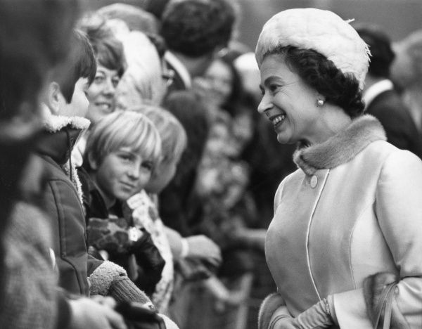 Queen Elizabeth II talks to children among the crowds during her walk through the Barbican Centre in London in November 1972. Date: 1972