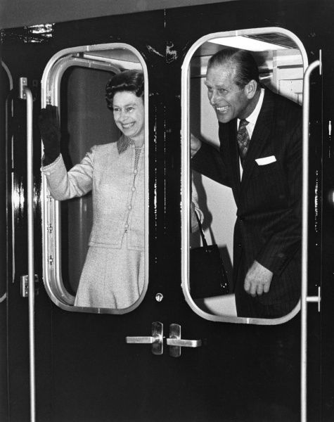 Queen Elizabeth II and the Duke of Edinburgh waving from a train in the year of the Silver Jubilee. Date: 1977