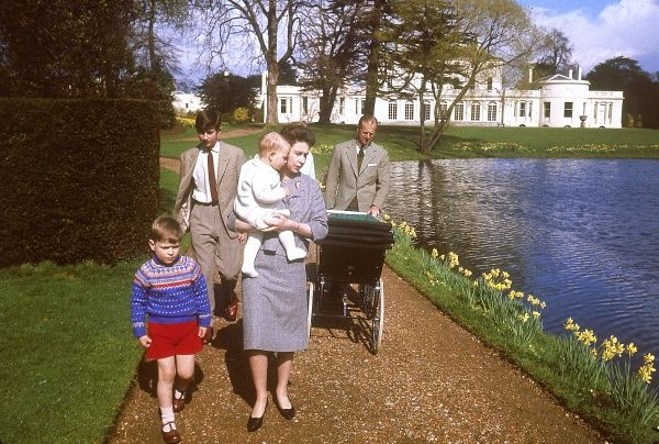 The royal family take a leisurely walk around the lake at Frogmore, The Queen holds the infant Prince Edward (Earl of Wessex) in her arms while four year old Prince Andrew walks alongside her. Bringing up the rear is Prince Charles and Princess Anne