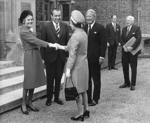 Queen Elizabeth II shakes hands with Mrs Pat Nixon, wife of the United States President, Richard Nixon who watches, along with British Prime Minister, Edward Heath, after the party had lunched at Chequers, the official British residence of the British premier
