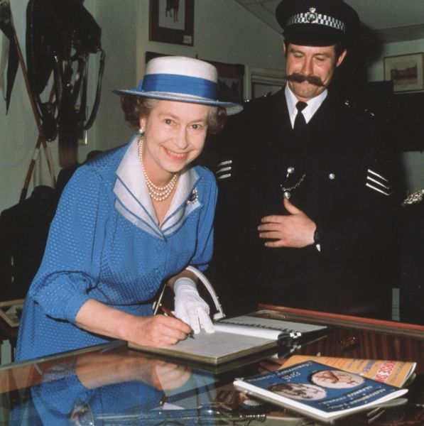 Queen Elizabeth II signing the visitors' book at a Metropolitan Police archive