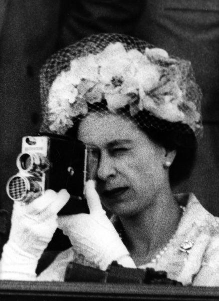Queen Elizabeth II spotted using a cine camera to capture the action of an event she is attending. Date: c.1965