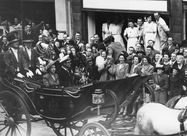 Princess Elizabeth (Queen Elizabeth II) and the Duke of Edinburgh passing through Fleet Street in London in an open-topped carriage on their way to the Guildhall where the Duke received the Freedom of the City of London. Date: 1948