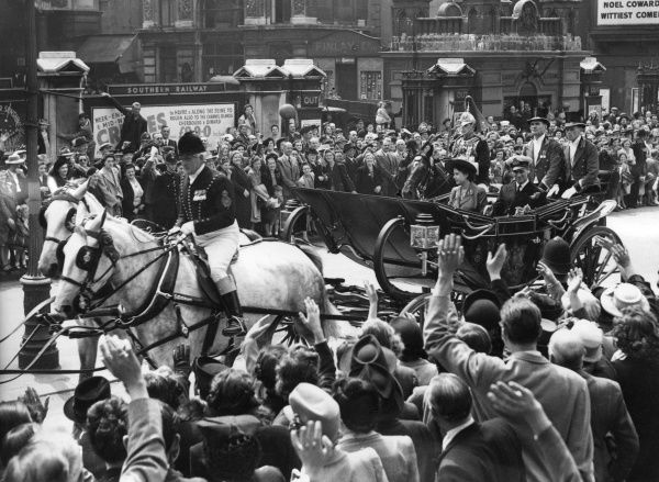 Princess Elizabeth and Prince Philip, Duke of Edinburgh, riding in a horse drawn, open-top carriage through the Strand, towards the Guildhall where the Duke received the freedom of the City. Date: 1948