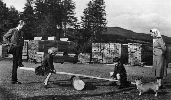 While the Queen looks on, Prince Philip, Duke of Edinburgh, rocks a see-saw for Prince Charles and Princess Anne during their visit to the farm and saw mill on the Balmoral Castle Estate in Scotland. Date: 1957