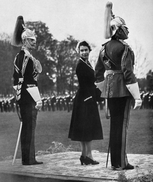 A young Queen Elizabeth II looks back over her shoulder as she waits for a parade of the Household Cavalry at Home Park, Windsor during a presentation of New Standards. She is flanked by the Colonel of the Royal Horse Guards, Maj-Gen Sir Richard Howard-Vyse