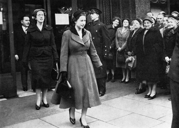 The Queen departs Harrods, Knightsbridge, London, after some early-morning Christmas shopping. During her time in the store she met the Duchess of Kent, also out shopping. Date: 1955
