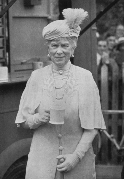 Queen Mary, consort of King George V, pictured during World War II enjoying a cup of tea from a mobile YMCA canteen in Cheltenham. Date: c.1943