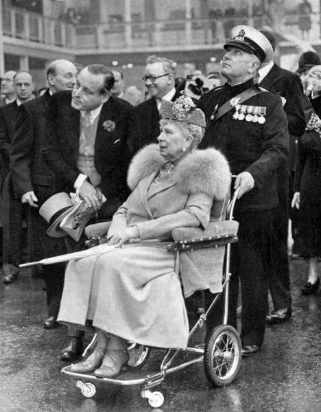 Queen Mary touring the pavilions of the Festival of Britain on the South Bank of London in a wheelchair. Date: 1951
