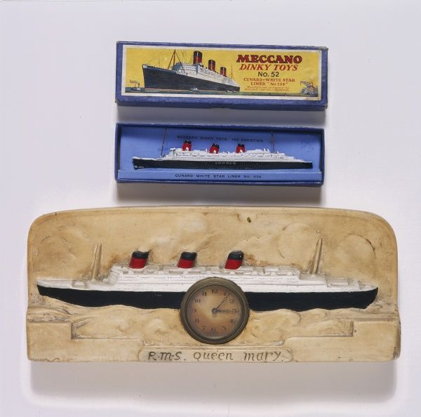 A commemorative clock with a model of the RMS Queen Mary, and a Meccano Dinky Toy no.52, both marking the launch of the Cunard cruise ship in 1935