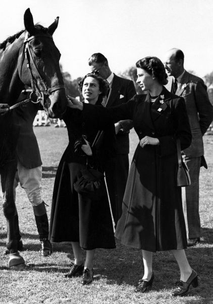 Queen Elizabeth II and Princess Margaret make friends with the famous 'Foxhunter' during the third day of the British Horse Society's Olympic Horse Trials at Badminton. Date: 1952