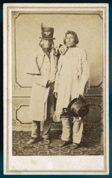 Two Digger Indians of the Yosemite Valley, photographed in a studio wearing elements of native and western dress, including a top hat with a bugle motif and feather