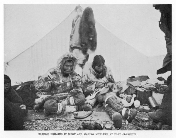 An Eskimo couple at Port Clarence, Alaska: he drills in ivory, she makes mukluks