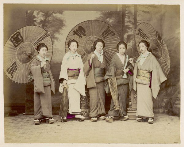 A group of geisha in their traditional dress with ornamental parasols