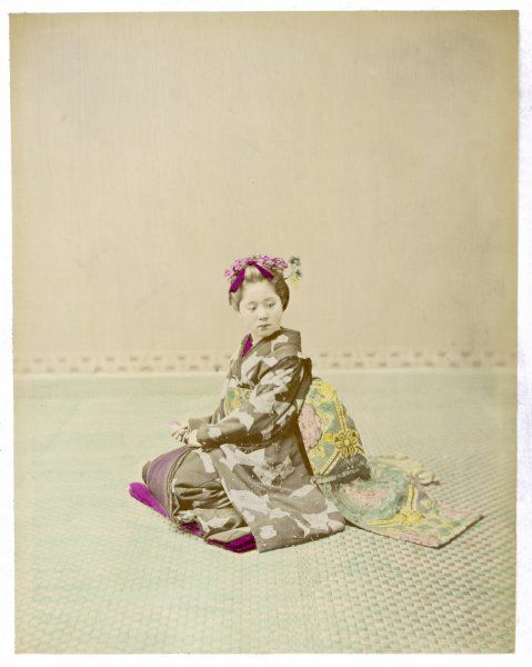 A girl (possibly an apprentice geisha) sitting in an elaborate and heavy kimono