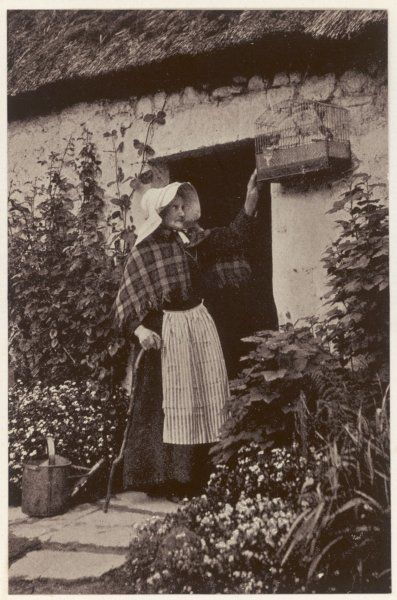 A Scottish countrywoman outside her thatched cottage