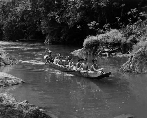 Iban women are as much at home as their menfolk, in a canoe on one of the mighty rivers of Borneo, Indonesia. Date: 1930s