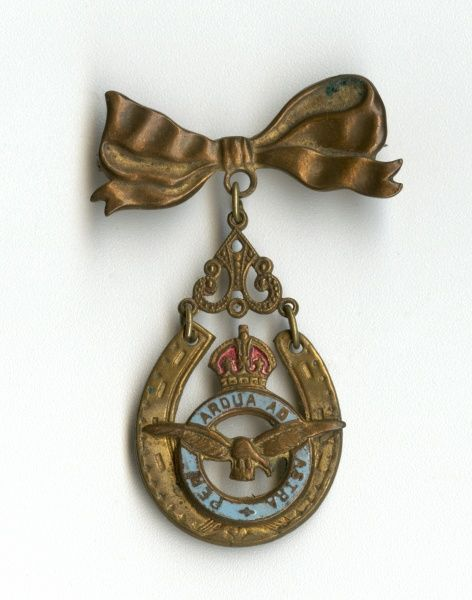 A Royal Air Force badge bearing the Latin motto Per Ardua Ad Astra (Through Adversity to the Stars), turned into a brooch by the addition of a bow and pin. Date: circa 1940s
