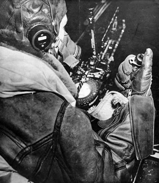 Photograph showing a Royal Air Force bomb-aimer at his position with the bomb release cable ready in his right hand, November 1943. The thick leather clothing required by air-crews to keep warm is clearly seen in this photograph