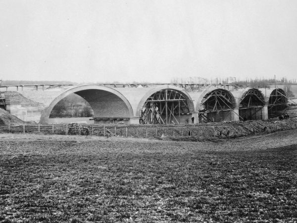 A railway bridge under construction somewhere on the Great Western Railway network, possibly at Princes Risborough in Buckinghamshire. A different stage of construction can be seen in each arch -- from right to left, centring, arch being bricked